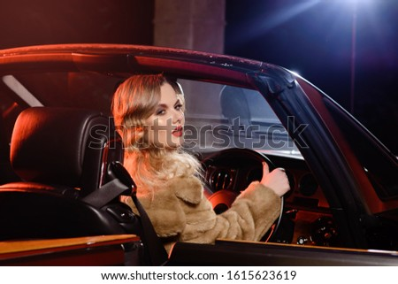 Retro portrait of a beautiful luxury Gatsby woman in black cabriolet car. Vogue fashion style and smoke. Cheerful woman rides to a party. Copy space