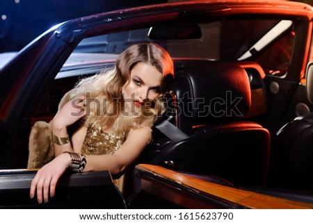 Retro portrait of a beautiful luxury Gatsby woman in black cabriolet car. Vogue fashion style and smoke. Hollywood look. Copy Space