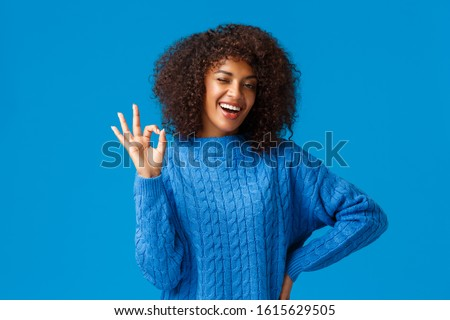 Count on me, everything ok. Cheerful and assertive african-american girlfriend with afro haircut have all under control, showing alright okay gesture and wink, smiling positive reply, blue background #1615629505