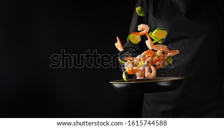 A professional chef cooks shrimp in a pan with brussels sprouts, vegetables. Cooking seafood, healthy vegetarian food and food on a dark background. Freezing in motion. Horizontal view. Banner. #1615744588