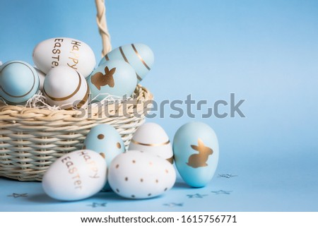 Easter colored eggs in a basket isolated on a trendy blue background. Minimal concept. Card with copy space for text. Royalty-Free Stock Photo #1615756771