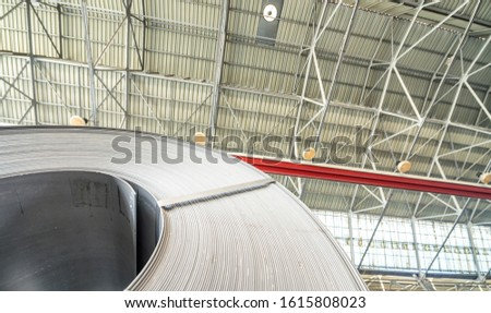 Industrial warehouse with rolls of steel sheet in a plant galvanized steel coil. Coil on foreground, ceiling on background #1615808023