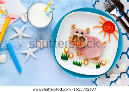 Fun food for kids - cute smiling hippo sandwich with ham and toast bread decorated with carrots, cucumbers and tomatoes for lunch.  #1615902697