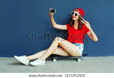 Happy smiling young woman taking selfie picture by smartphone sitting on skateboard wearing red baseball cap, shorts on city street over blue wall background