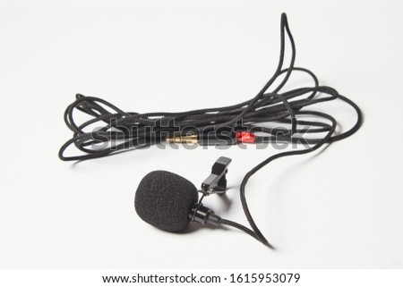 Small lavalier microphone isolated on white background. Professional sound recording equipment. Lapel mic.