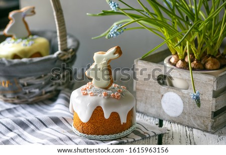 On grey wooden table and Easter Bunny cake, Easter cake in a basket or in a wooden, grey box, spring flowers Muscari, sweet table for the holiday, Easter Holiday, Easter decor. #1615963156