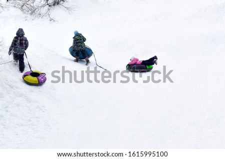Children play in the winter in nature. Boy pulls snow tubes in the park. Winter recreation, active lifestyle, childhood. Blurred background. Place for text.  Climb a snow hill. Back view. #1615995100