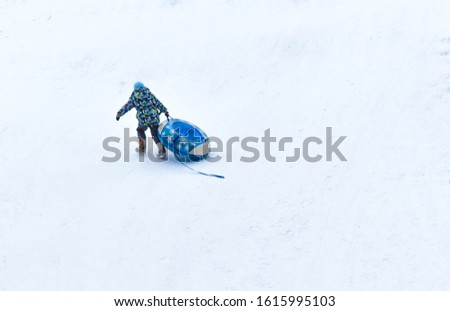 Boy pulls snow pipes in a park. Winter holidays. Blurred background. Back view. Active games. Climb a snow hill.  Place for text. #1615995103
