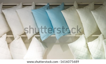 White blue pillows, lots of pillows on a store shelf. Bedding, comfortable quilted pillow for sleeping. Soft cotton natural fabric material #1616075689