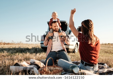 Happy Young Family Mom and Dad with Their Little Son Enjoying Summer Weekend Picnic Sitting on the Plaid Near the Car Outside the City in the Field at Sunny Day Sunset, Vacation and Road Trip Concept #1616122150