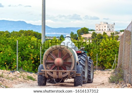 Farmer wearing protective clothes drives a tractor on a lemon plantation in Spain. Farmer about to spray pesticide and insecticide. Weed insecticide fumigation. Organic ecological agriculture.  #1616137312