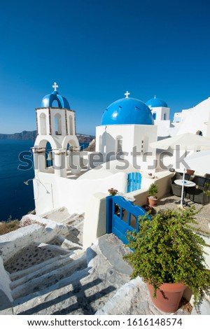 Bright scenic view of the Mediterranean hillside village of Oia in Santorini, Greece with gate matching sky blue Greek church domes  #1616148574