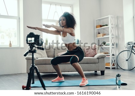 Beautiful young African woman crouching using strap while making social media video #1616190046