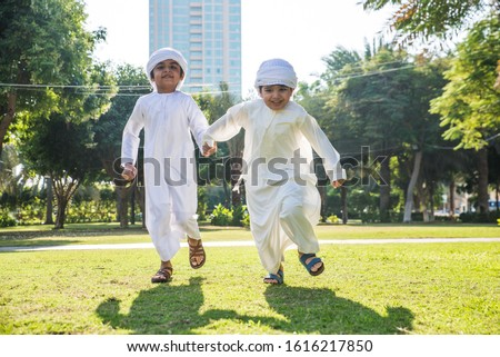 Children playing together in Dubai in the park. Group of kids wearing traditional kandura white dress from arab emirates Royalty-Free Stock Photo #1616217850