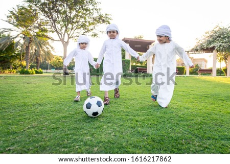 Children playing together in Dubai in the park. Group of kids wearing traditional kandura white dress from arab emirates Royalty-Free Stock Photo #1616217862