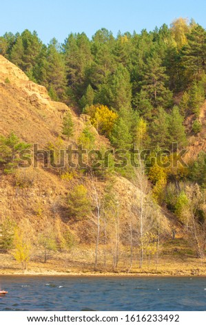 Autumn landscape, dark blue water, last warm days, river, trees, windy weather, yellow-red autumn leaves #1616233492