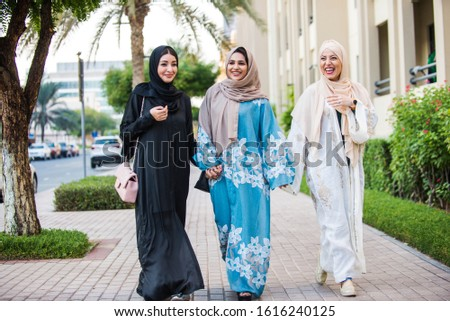 Three women friends going out in Dubai. Girls wearing the united arab emirates traditional abaya Royalty-Free Stock Photo #1616240125
