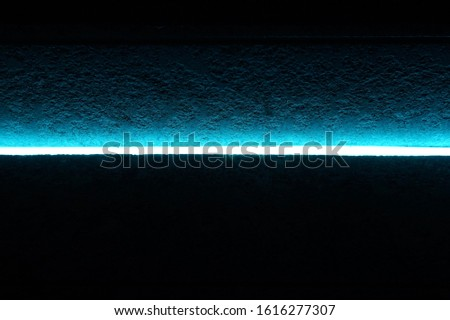A narrow blue neon light glows in the dark to partly illuminate a rough cement surface #1616277307