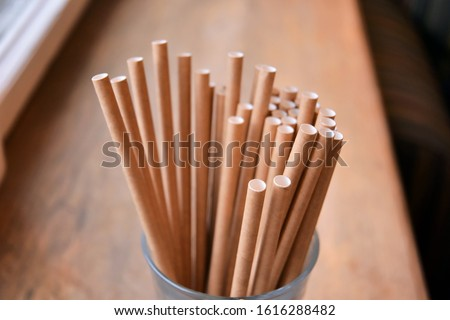 Eco friendly Reusable Straws in the cardboard cup with selective focus and blurred ba. Paper cocktail tubes. Kraft paper straw for drinking coffee or tea. Disposable cocktail tube.  #1616288482