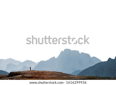 Distant tiny person in a background of mountains range isolated on white background, lonely hiker looking at view in vast environment