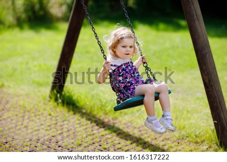 Cute adorable toddler girl swinging on outdoor playground. Happy smiling baby child sitting in chain swing. Active baby on sunny summer day outside #1616317222