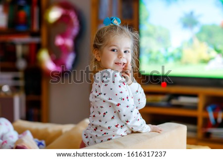 Cute little toddler girl in nightwear pajamas watching cartoons or movie on tv. Happy healthy baby child at home.