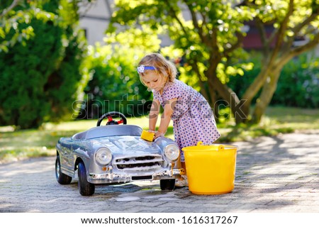 Cute gorgeous toddler girl washing big old toy car in summer garden, outdoors. Happy healthy little child cleaning car with soap and water, having fun with splashing and playing with sponge. Royalty-Free Stock Photo #1616317267