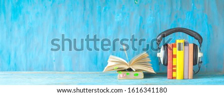 Open book, row of books and headphones, audio book concept, panorama format on grungy background, good copy space