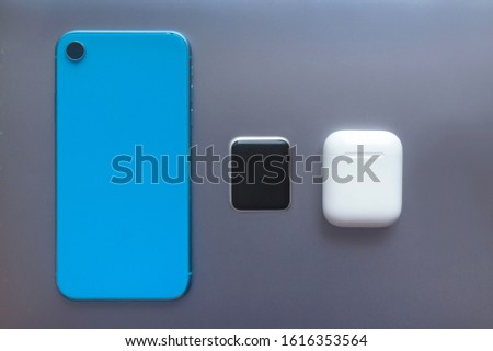 New modern gadgets, devices: blue cell mobile smartphone, smartwatches and case with wireless earphones or headphones on dark gray laptop. Technology concept. Top view. #1616353564