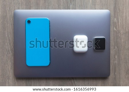 New modern gadgets, devices: laptop, notebook, blue cell mobile smartphone, smartwatches and case with wireless earphones or headphones on dark gray laptop. Technology concept. Top view. #1616356993