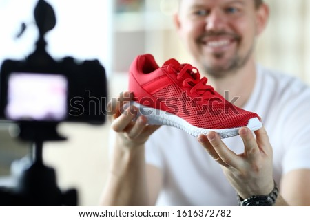 Male product reviewer tells his subscription in an online broadcast how to recognize signs of originality and fake sports sneakers closeup. Consultant seller education concept