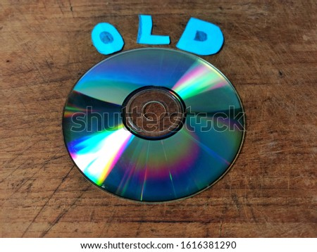 Compact disk on wooden board and the word old. obsolete technology concept #1616381290