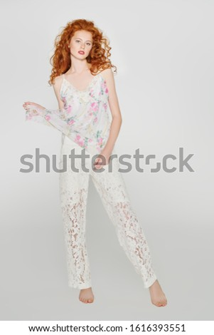 Beautiful fashion model with long curly hair posing at studio. Light summer style. White background. Full length portrait. Copy space.  #1616393551