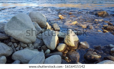 Photo of a pile of rocks on the shore with flowing water in the background. #1616415142