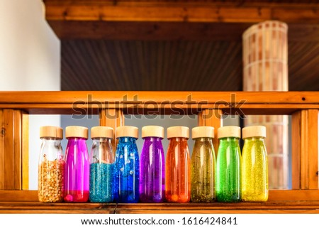 Collection of bottles of calm, plastic with wooden stopper, toy filled with liquids and materials of bright colors and glitter to relax children when they are nervous. #1616424841