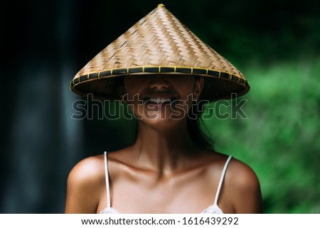 Portrait of a beautiful girl in an Asian conical hat. Portrait of a smiling girl. Beautiful smile. Close-up smile. Funny girl. Smiling girl. Funny portrait. A woman in a Balinese conical hat. #1616439292