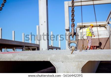 Worker is preparing crane hook for unloading concrete joist from truck trailer. #1616442391