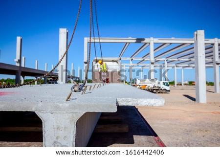 Worker is preparing crane hook for unloading concrete joist from truck trailer. #1616442406