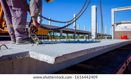 Worker is preparing crane hook for unloading concrete joist from truck trailer. #1616442409
