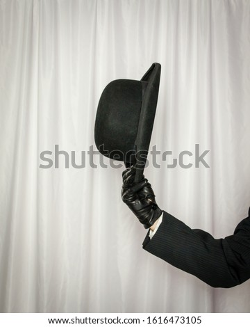 Isolated Arm of Man Wearing Dark Suit and Doffing Bowler Hat #1616473105