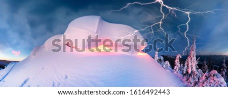 snow cornice at the top is a snow formation formed in the mountains under the influence of wind. Artistic illumination has created a fabulous fiction picture, lightning hit the top of the mountain