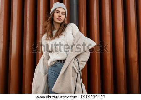 Young beautiful woman model in stylish youth warm outerwear posing near a modern wall on the street. Attractive girl in fashionable clothes is standing in the city. New spring collection. Style. Royalty-Free Stock Photo #1616539150