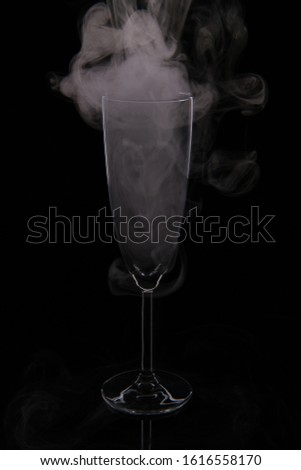 A glass glass glass for champagne filled with smoke on a black background. #1616558170