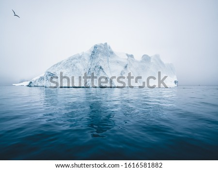 Iceberg and ice from glacier in arctic nature landscape in Ilulissat, Greenland. Aerial drone photo of icebergs in Ilulissat icefjord. Affected by climate change and global warming. #1616581882