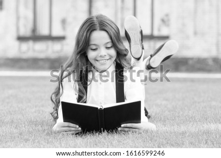 Basic education. Adorable little girl learn reading. Schoolgirl school uniform laying on lawn with favorite book. Studying concept. Extracurricular reading. Cute small child reading book outdoors. #1616599246