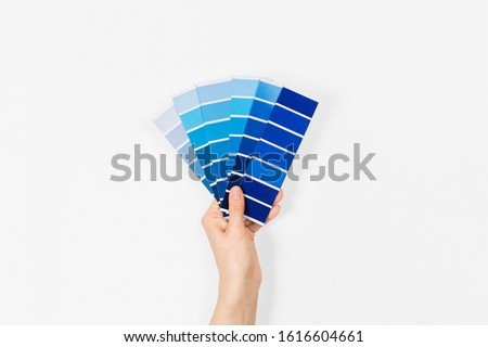 Color swatches with color of the year 2020 in the hand - Classic Blue. Color trend palette. Top view, flat lay.