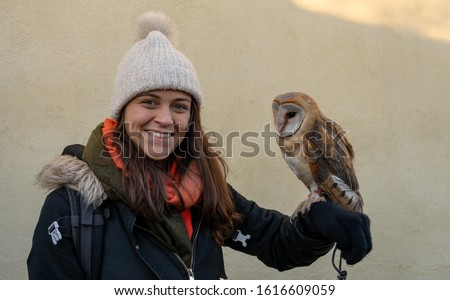 Portrait picture of a girl with an owl on her arm