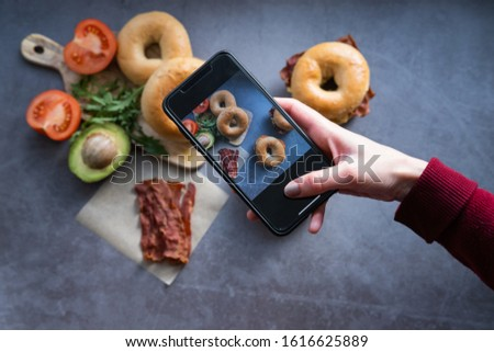 Hand's woman taking a picture with a mobile phone of a salmon bagel and a bacon bagel. Blogging concept.