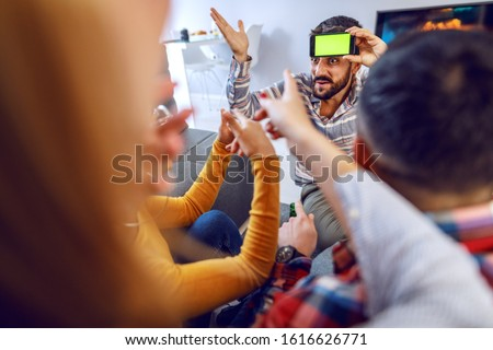 Group of cheerful playful friends playing charades with smart phone. Home interior. #1616626771