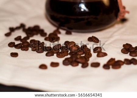 One-tone light background of coarse fabric. Arabica coffee beans are scattered. Caffeine drink. #1616654341
